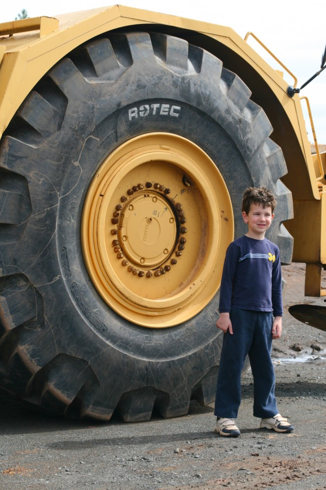 Ethan in front of the tire of a huge construction truck
